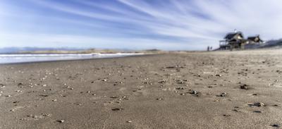 Praia com conchas e casa de temporada ao fundo